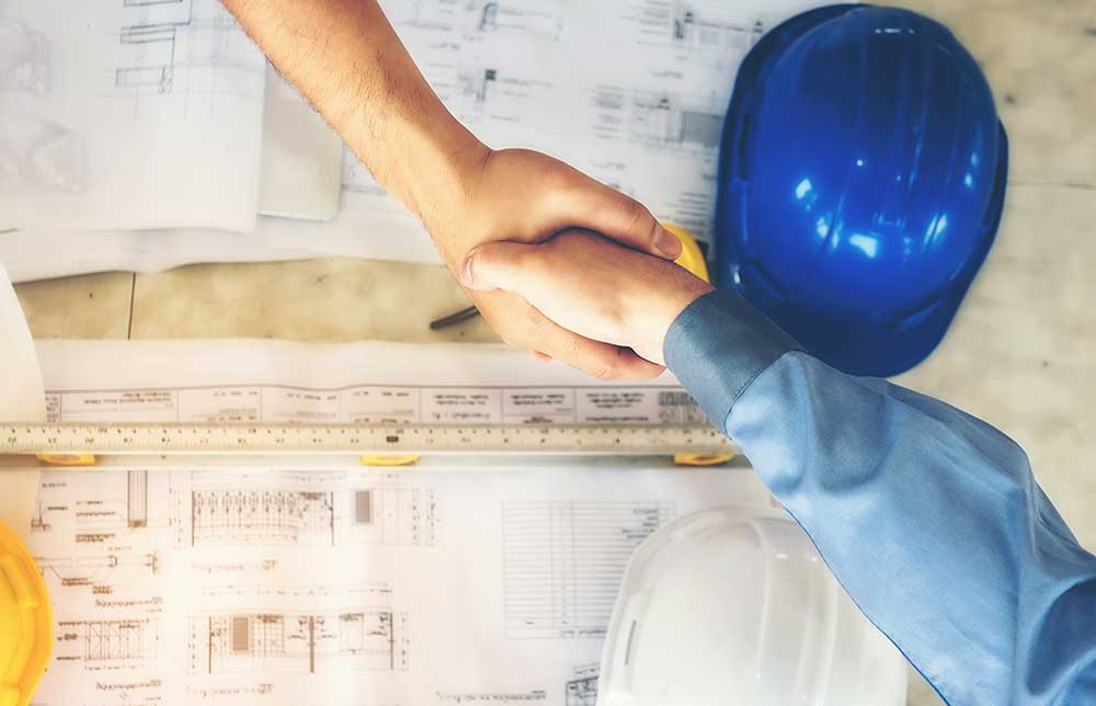 engineers shaking hands over detailed drawings