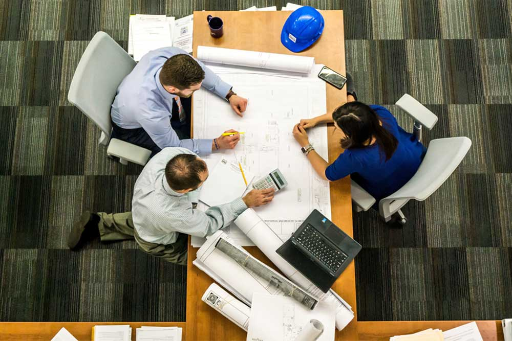 engineers working around a table discussing pricing of a construction project