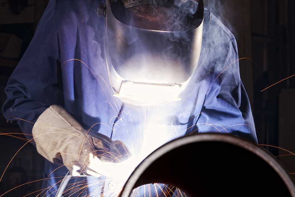 pipe fabrication welder working on the end of a pipe with yellow sparks and smoke